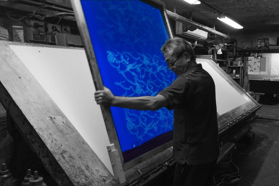 株式会社 伊地智写真型製作所(シルクスクリーン)の作業現場の写真 作業現場で職人がシルクスクリーンを運んでいる風景