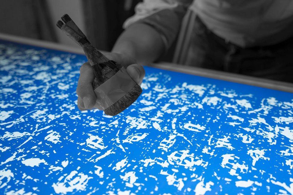 株式会社 伊地智写真型製作所(シルクスクリーン)の作業現場の写真 シルクスクリーンの汚れやほこりを取り除く作業の風景